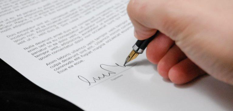 Foto van iemand die zijn handtekening zet