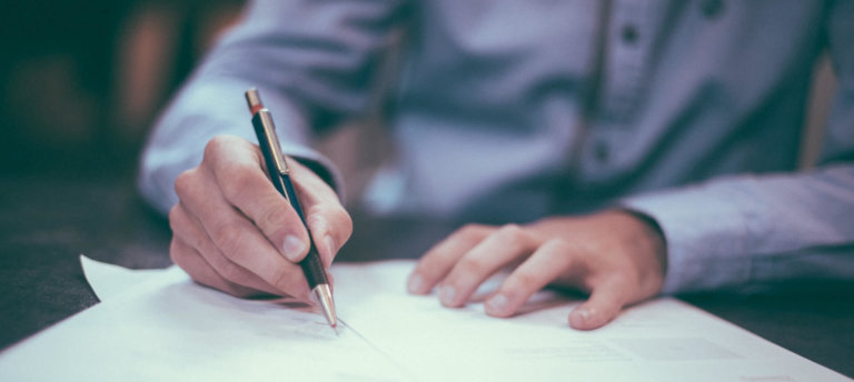 Een man die op een papier aan het schrijven is